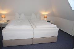Schlafzimmer mit Boxspringbetten und Blick in den Giebel im 2.. OG.